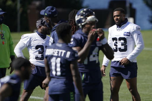 Seattle Seahawks safety Jamal Adams (33) stands on the field with teammates during NFL football training camp, Tuesday, Sept. 1, 2020, in Renton, Wash. (AP Photo/Ted S. Warren)