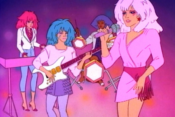 """<p>No, we're not talking about the 2015 live-action film. The original cartoon series is about Jem, the lead singer, and her musical group, """"the Holograms,"""" who are also her adopted sisters. Jem is a predecessor of Hannah Montana — her real name is Jerrica Benton, but her identity is hidden due to holographic technology that disguises her as the rock star. As a devoted sisterhood, the band protects her identity. <i>(Source: Hasbro)</i></p>"""