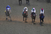 John Velazquez rides Medina Spirit, right, leads Florent Geroux on Mandaloun, Flavien Prat riding Hot Rod Charlie and Luis Saez on Essential Quality to win the 147th running of the Kentucky Derby at Churchill Downs, Saturday, May 1, 2021, in Louisville, Ky. (AP Photo/Charlie Riedel)