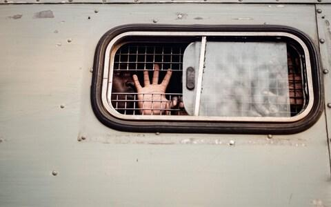 A supporter of the opposition MDC Alliance gestures the party's symbol from inside of a prison truck - Credit: ZINYANGE AUNTONY/AFP/Getty Images