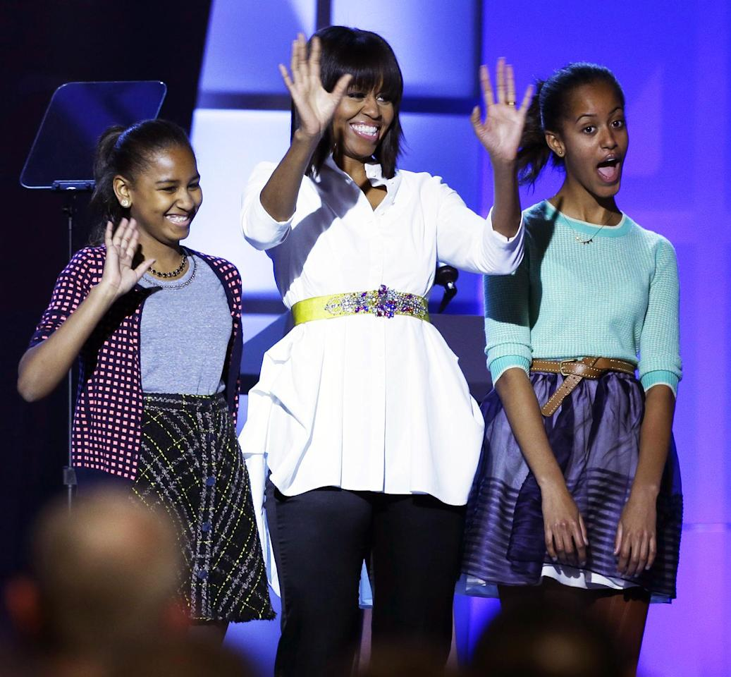 """First lady Michelle Obama, center, and daughters Sasha, left, and Malia, right, react during the Kids' Inaugural: Our Children. Our Future."""" event in Washington, Saturday, Jan. 19, 2013, as part of the 57th Inauguration weekend of events. (AP Photo/Frank Franklin II)"""