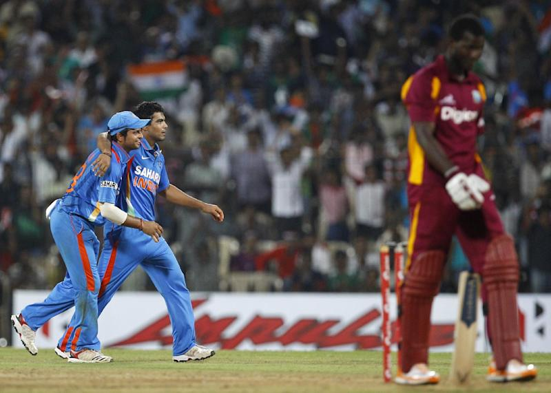 India's bowler Ravindra Jadeja, second left, celebrates with teammate Suresh Raina, left, after the dismissal of West Indies' captain Darren Sammy, right, during their fifth one-day international cricket match in Chennai, India, Sunday, Dec. 11, 2011. (AP Photo/Aijaz Rahi)