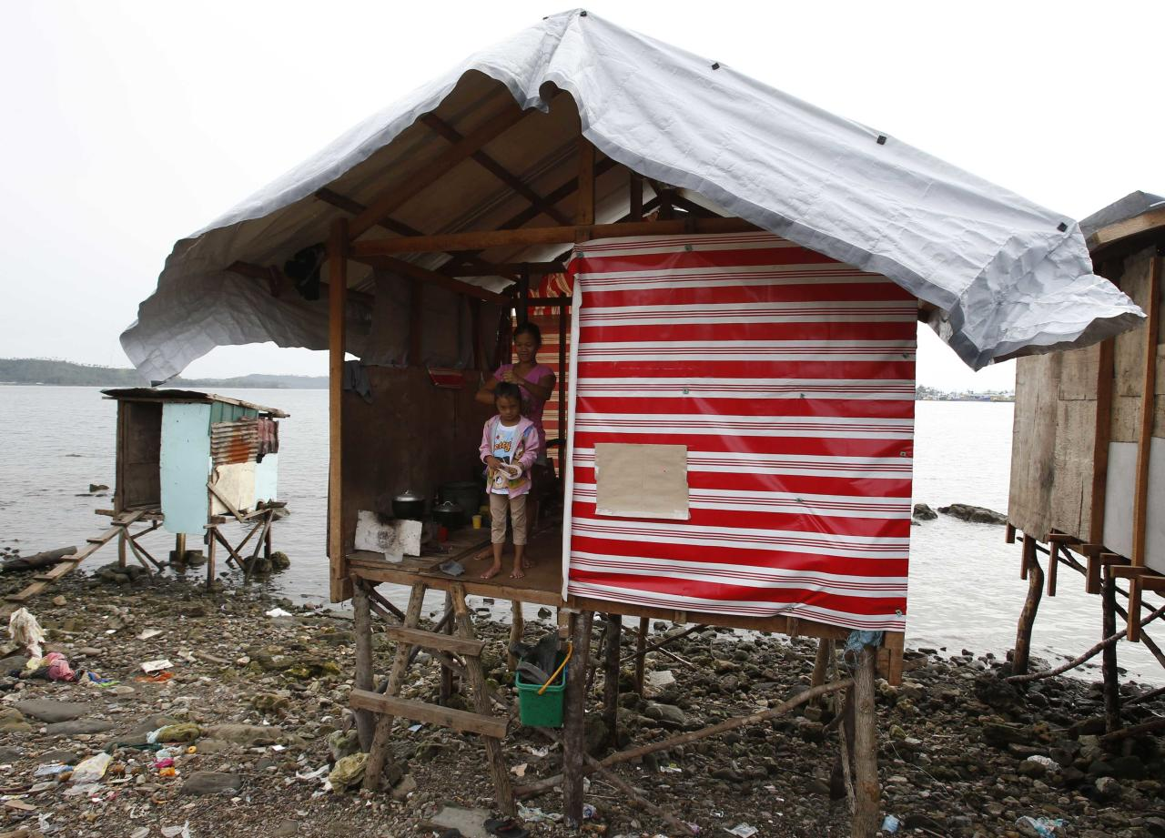 Typhoon survivors are seen at the entrance of a temporary shelter nearly 100 days after super Typhoon Haiyan devastated Tacloban city in central Philippines February 14, 2014. Typhoon Haiyan killed more than 6,200 people and left tens of thousands homeless when it struck in November last year. REUTERS/Erik De Castro (PHILIPPINES - Tags: DISASTER ENVIRONMENT SOCIETY)