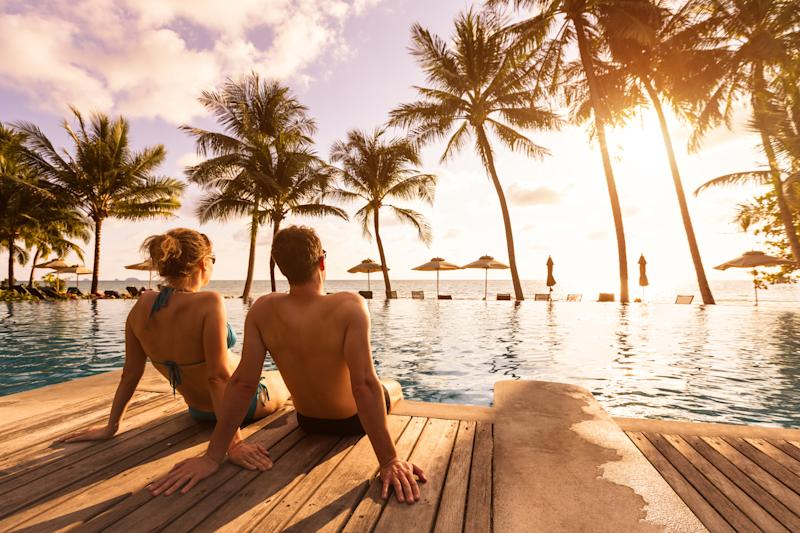 Couple enjoying beach vacation holidays at tropical resort. Photo: Getty