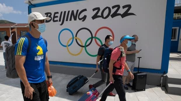 Visitors to Chongli, one of the venues for the 2022 Beijing Games, pass by the Olympics logo. A multi-party group of Canadian MPs have called for the Olympics to be relocated over reported human rights abuses against ethnic minorities in China.