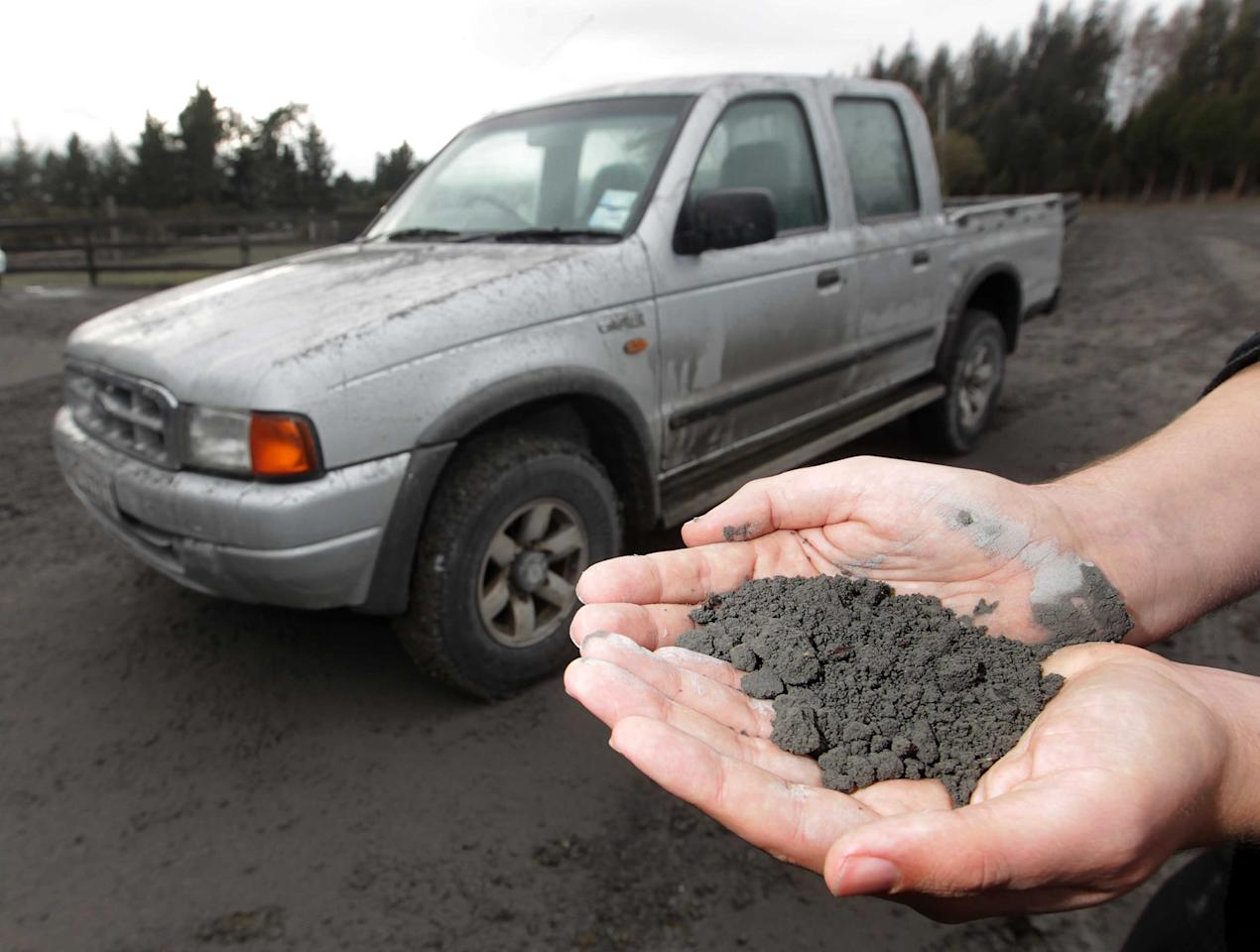 A man holds a handful of volcanic ashes that fell on a property in Rangipo near the base of Mt Tongariro, New Zealand after an eruption Tuesday, Aug. 7, 2012. The volcano in New Zealand's central North Island has erupted for the first time in more than a century, sending out an ash cloud that is causing road closures and the cancellation of some domestic flights. (AP Photo/New Zealand Herald, Alan Gibson) AUSTRALIA OUT, NEW ZEALAND OUT