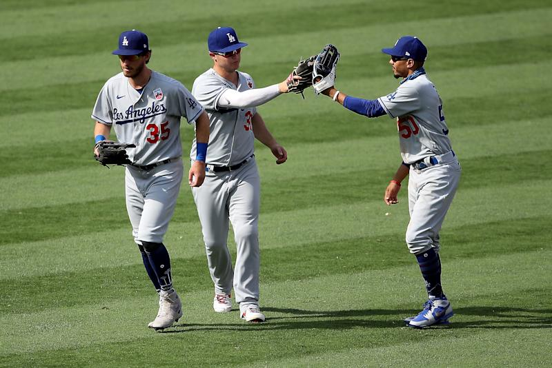 ANAHEIM, CALIFORNIA - AUGUST 16: Joc Pederson #31, Cody Bellinger #35 and Mookie Betts #50 of the Los Angeles Dodgers celebrate defeating the Los Angeles Angels 8-3 in a game at Angel Stadium of Anaheim on August 16, 2020 in Anaheim, California. (Photo by Sean M. Haffey/Getty Images)