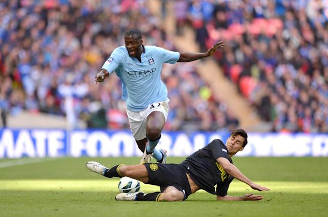 Manchester City's Yaya Toure and Wigan Athletic's Paul Scharner (right) battle for the ball
