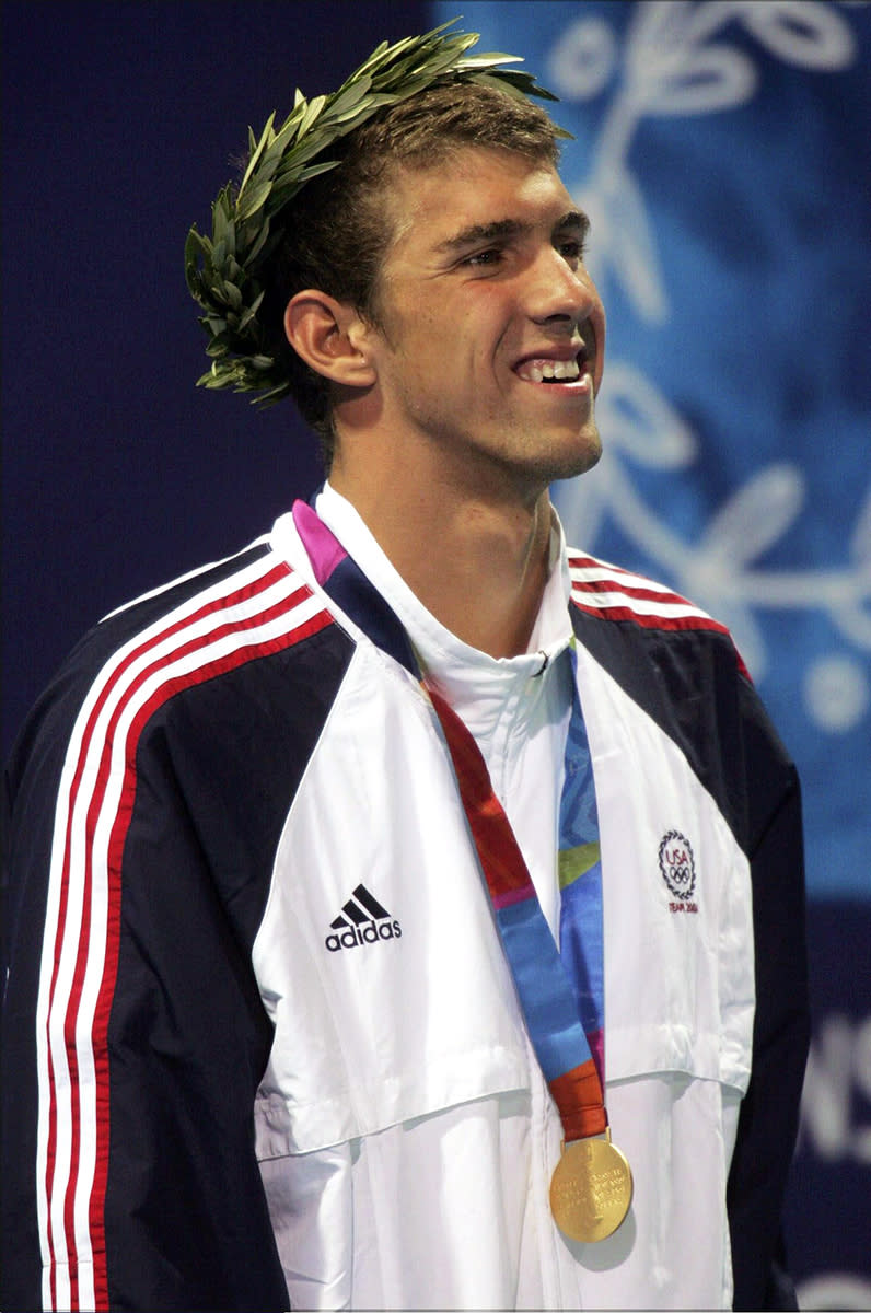<p>Michael Phelps stands on the podium with his gold medal for the 200-meter individual medley on August 19, 2004 at the Athens Olympics. (Alexander Hassenstein/Bongarts/Getty Images)</p>