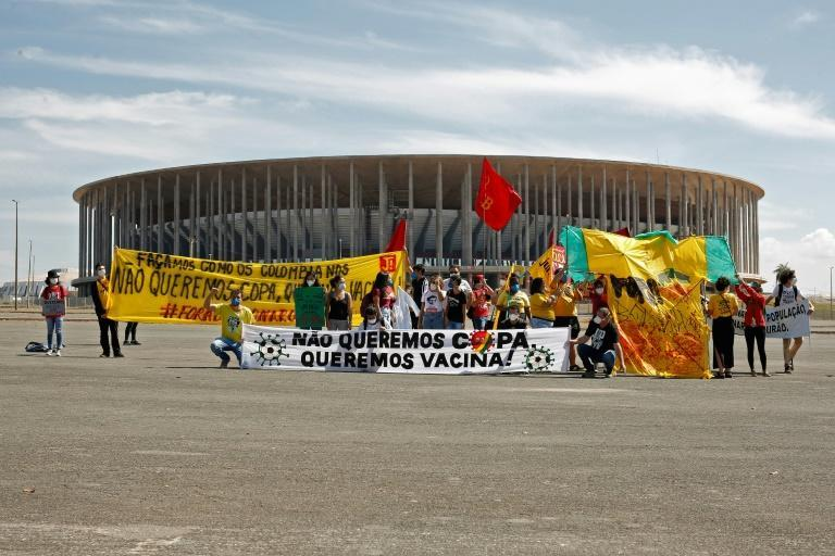 Demonstrators stand behind a banner reading 'We don't want the Copa, we want vaccines' outside the Mane Garrincha stadium before the Copa America opening game