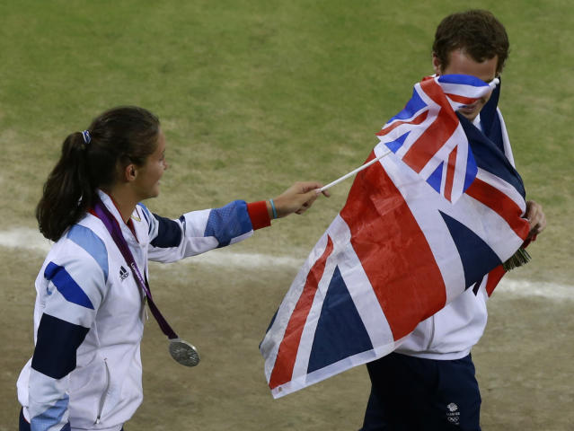 Silver medallists Andy Murray and Laura Robson of Britain play with a flag during the presentation ceremony for tennis mixed doubles at the All England Lawn Tennis Club during the London 2012 Olympic Games August 5, 2012. REUTERS/Adrees Latif (BRITAIN - Tags: OLYMPICS SPORT TENNIS)