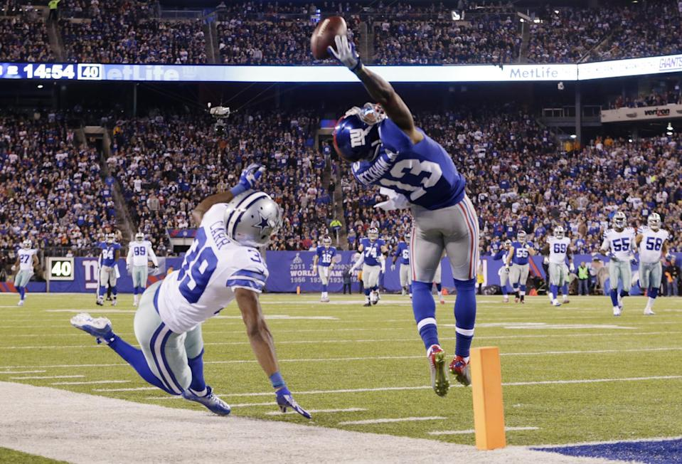 FILE - In this Nov. 23, 2014, file photo, New York Giants wide receiver Odell Beckham Jr. (13) makes a one-handed catch for a touchdown against Dallas Cowboys cornerback Brandon Carr (39) in the second quarter of an NFL football game in East Rutherford, N.J. The one-handed catch by Odell Beckham Jr. that became the most talked-about play from Sunday did more than just boost his standing with the New York Giants, it paid off a routine growing popular among many skill players of practicing the impractical, one-handed circus grab. (AP Photo/Julio Cortez, FILE)