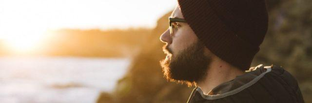 photo of man with beard wearing coat and hat and looking out over sea at sunset or sunrise