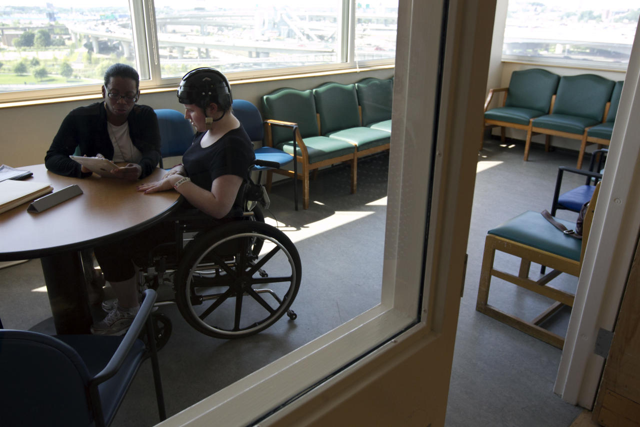 In this Wednesday, July 11, 2012 photo, Meg Theriault of Salisbury, Mass., works with speech therapist Lynette Holmes, left, at the Spaulding Rehabilitation Hospital in Boston. Meg is being tutored in speech therapy as part of her rehabilitation from a near-fatal traumatic brain injury. (AP Photo/Steven Senne)