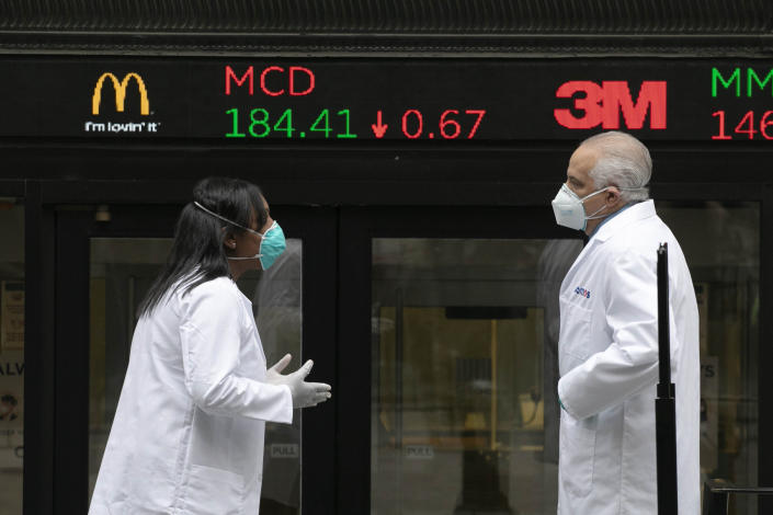 IMAGE DISTRIBUTED FOR THE NEW YORK STOCK EXCHANGE - Health care screeners talk outside the New York Stock Exchange, as the trading floor partially reopens on Tuesday, May 26, 2020, in New York. The floor, known worldwide for an anarchic atmosphere with traders shouting orders over one another, has been closed since mid-March due to the coronavirus outbreak. The NYSE says fewer traders will be on the floor at a given time for now in order to support six-feet social distancing requirements. They also must wear masks. (Mark Lennihan/AP Images for THE NEW YORK STOCK EXCHANGE )