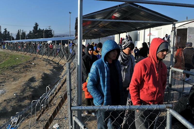 Migrants and refugees line up to receive food as they wait to cross the border from Greece to Macedonia near Idomeni, on January 21, 2016 (AFP Photo/Sakis Mitrolidis)