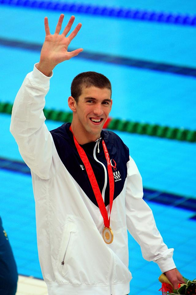 BEIJING - AUGUST 16:  Gold medalist Michael Phelps of the United States waves during the medal ceremony for the Men's 100m Butterfly Final held at the National Aquatics Centre during Day 8 of the Beijing 2008 Olympic Games on August 16, 2008 in Beijing, China. By winning gold in the Men's 100m Butterfly Phelps tied Mark Spitz's record of winning seven gold medals in a single Olympic Games.  (Photo by Jamie Squire/Getty Images)