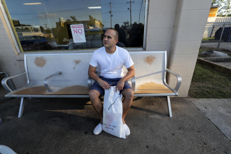 "Pedro Cordoves Diaz, a 26-year-old from Cuba who was just released from the Winn Correctional Center, waits with his sole bag of belongings, at a bus station over 55 miles away, to travel to relatives in New Jersey, in Alexandria, La., Thursday, Sept. 26, 2019. He had been denied parole, but was ultimately given his release on $10,000 bond, paid by relatives in New Jersey. ""I stayed in my bed waiting for the moment to leave to arrive,"" Diaz said. (AP Photo/Gerald Herbert)"