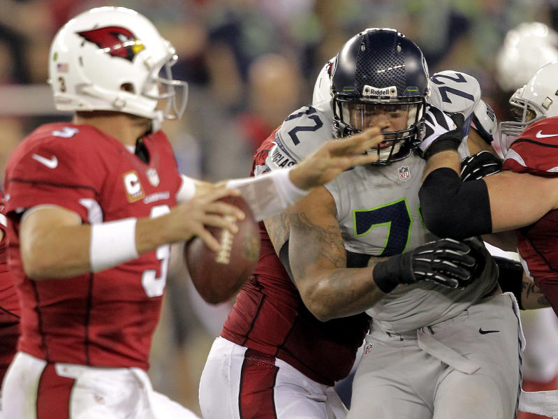 Arizona Cardinals quarterback Carson Palmer (3) is pressured by Seattle Seahawks defensive end Michael Bennett (72) during the first half of an NFL football game, Thursday, Oct. 17, 2013, in Glendale, Ariz. (AP Photo/Rick Scuteri)