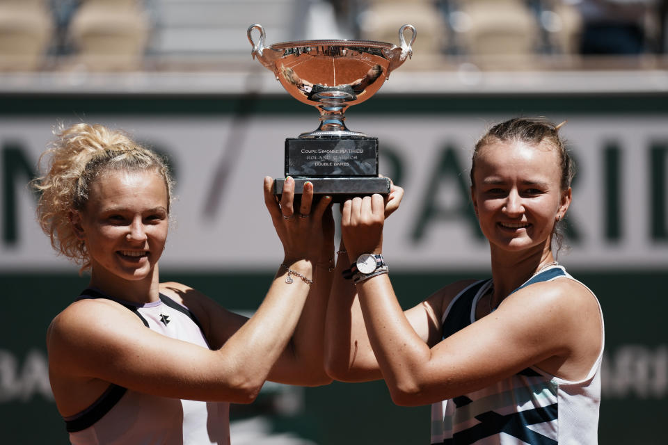 Czech Republic's Barbora Krejcikova, right, and compatriot Katerina Siniakova hold the cup after defeating USA's Bethanie Mattek-Sands and Poland's Iga Swiatek in their women's doubles final match of the French Open tennis tournament at the Roland Garros stadium Sunday, June 13, 2021 in Paris. (AP Photo/Thibault Camus)