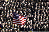 FILE - In this Dec. 1, 2001, file photo, the American flag flies with a background of Navy midshipmen during the national anthem at the 102nd Army Navy NCAA college football game in Philadelphia. Twenty years later, former Army football coach Todd Berry still gets choked up thinking about that Sept. 11, 2001, day and the terrorist attacks carried out not only on the twin towers at the World Trade Center but at the Pentagon, and in a field in rural Pennsylvania. (AP Photo/Chris Gardner, File)