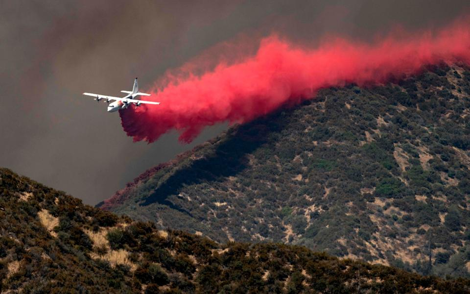 A firefighting plane makes a low-flying retardant drop on a ridge as firefighters continue to battle the Apple Fire - JOSH EDELSON/AFP