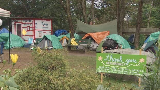 A sign at Meagher Park in Halifax thanks neighbours for their 'love, care, offerings, interest, compassion, participation, support, solidarity and welcome.' People experiencing homelessness have set up tents and other shelters in the park. (CBC - image credit)