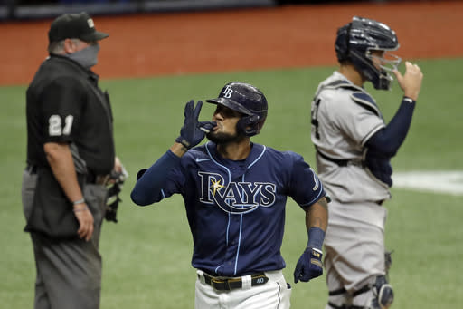 Tampa Bay Rays' Jose Martinez, center, celebrates after his two-run home run off New York Yankees starting pitcher Gerrit Cole during the fifth inning of the first game of a doubleheader baseball game Saturday, Aug. 8, 2020, in St. Petersburg, Fla. In the background are home plate umpire Hunter Wendelstedt, and Yankees catcher Gary Sanchez. (AP Photo/Chris O'Meara)