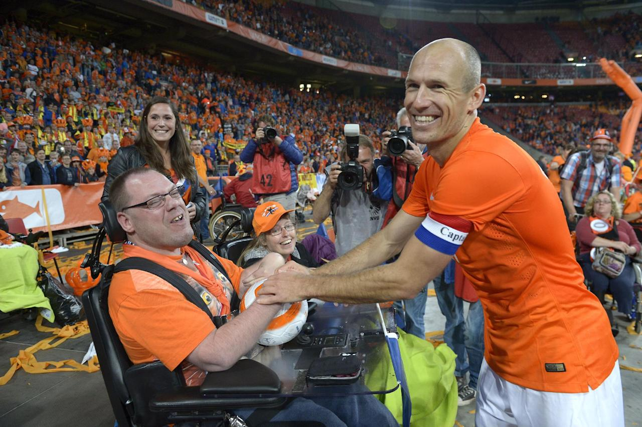 Dutch player Arjen Robben greets fans after the match against Wales at ArenA stadium in Amsterdam, Netherlands, Wednesday June 4, 2014. (AP Photo/Ermindo Armino)