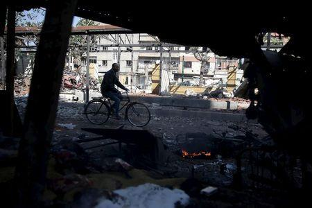 A man rides a bicycle at a damaged site hit by missiles fired by Syrian government forces on a busy marketplace in the Douma neighborhood of Damascus, Syria October 30, 2015. REUTERS/Bassam Khabieh