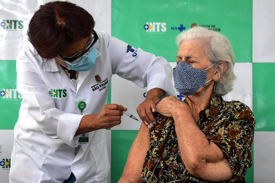 An elderly woman is inoculated with Chinese Coronavac against COVID-19, on the first day of immunization of people over 90 years-old, in Sao Paulo, Brazil, on February 5, 2021. (Photo by NELSON ALMEIDA / AFP) (Photo by NELSON ALMEIDA/AFP via Getty Images)