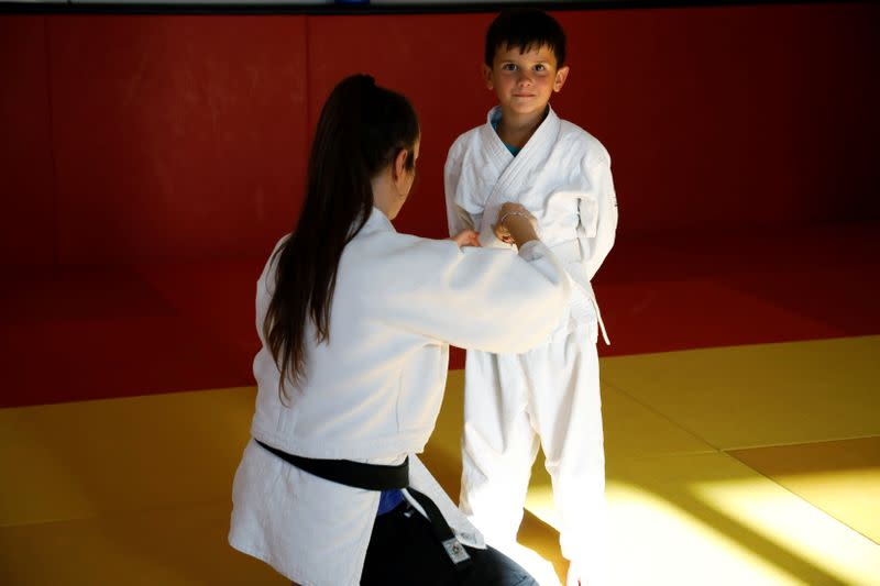 A child looks at the camera as he is being helped to prepare for Judo training at the Ippon judo club in Peja