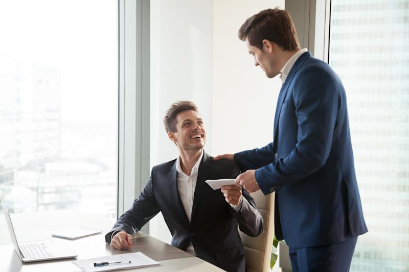 A standing man handing a male seated employee an envelope.