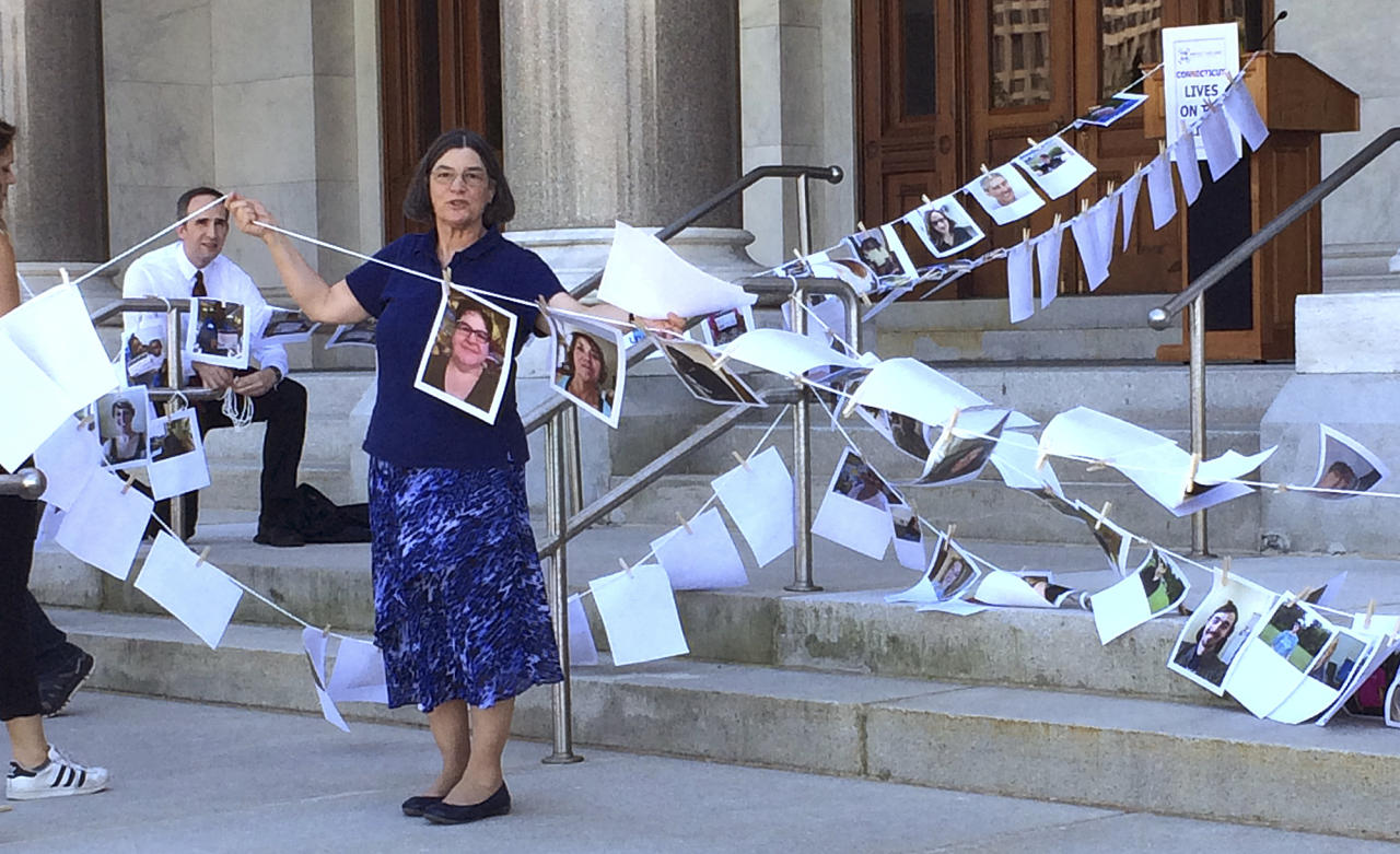 """Jane McNichol, an organizer of the Protect Our Care CT campaign, holds up a clothesline with photos of Connecticut residents opposed to repeal of the Affordable Care Act, during a rally on the state Capitol steps, Thursday, June 22, 2017, in Hartford, Conn. The group gathered to demonstrate their position that Connecticut lives are """"on the line"""" as Senate Republicans launched their plan in Washington for peeling back former President Barack Obama's health care law. (AP Photo/Susan Haigh)"""