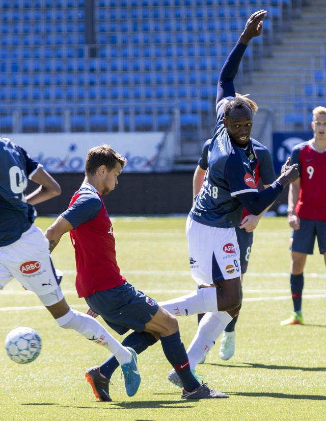 Jamaican sprint legend Usain Bolt, right, and Norway's U19 player Tord Johnsen Salte battle for the ball during the friendly soccer match between Stromsgodset and Norway's U19 team at Marienlyst Stadium in Drammen, Norway, Tuesday June 5, 2018. (Vidar Ruud/NTB Scanpix)