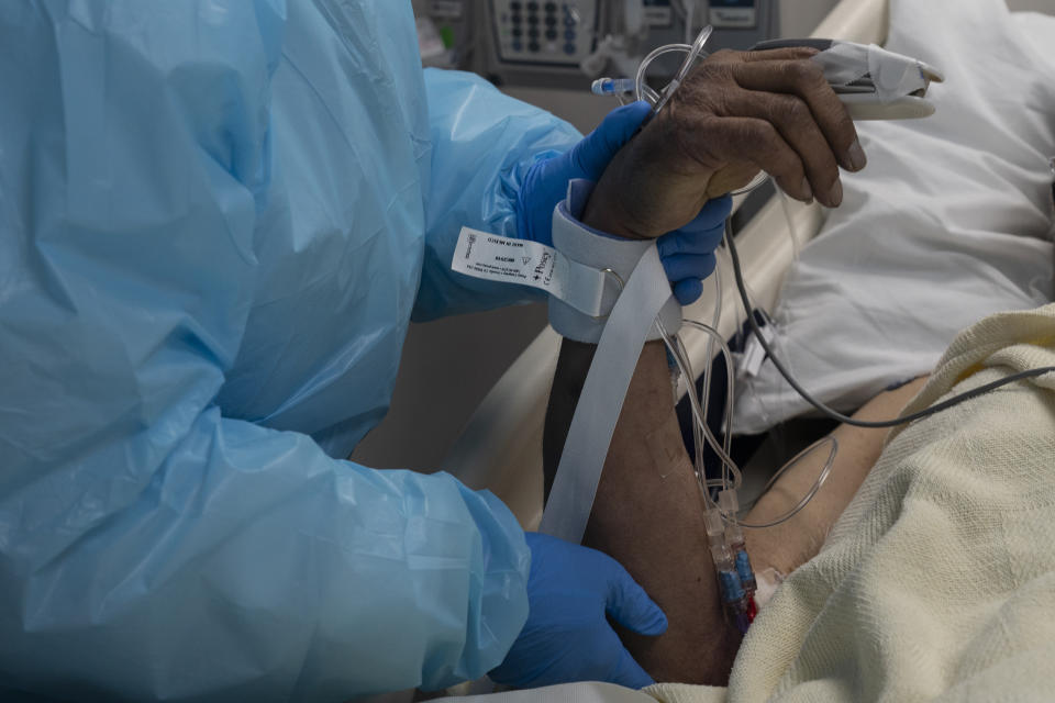 A medical staff member holds a hand of a patient