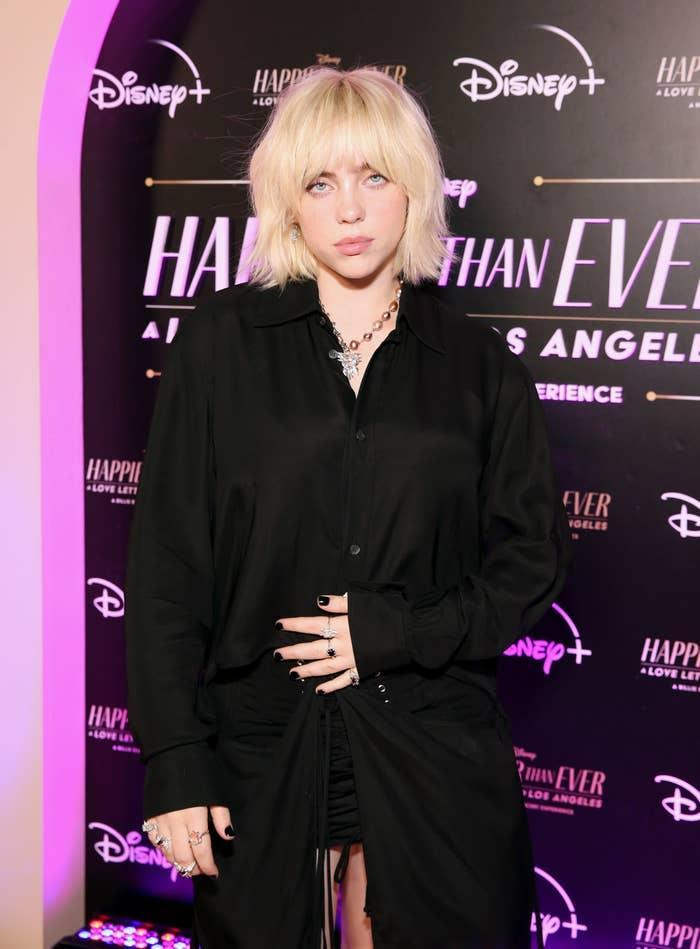 Billie on a red carpet wearing a dark colored blouse and matching skirt