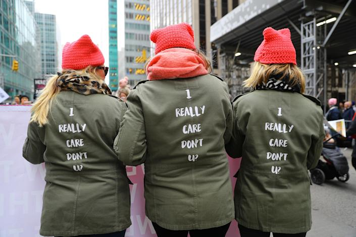 Three sisters march up Sixth Avenue wearing a jacket made famous by U.S. First Lady Melania Trump as they participate in the Women's March in New York City on Jan. 19, 2019 in New York City. (Photo: Gordon Donovan/Yahoo News)