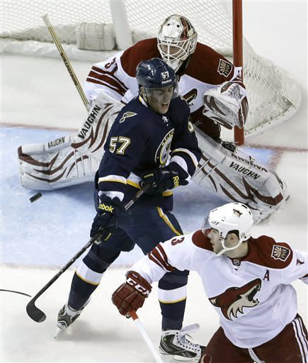 St. Louis Blues' David Perron (57) deflects the puck to score past Phoenix Coyotes goalie Chad Johnson, top, as Coyotes' Keith Yandle, bottom, watches during the first period of an NHL hockey game on Thursday, April 18, 2013, in St. Louis. (AP Photo/Jeff Roberson)
