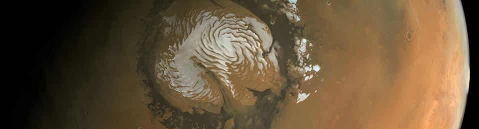 Spiral troughs of ice and dust swirl around the Red Planet's polar ice cap in this image of the planet's north pole. Citizen scientist Kevin Gill created this map using images from the European Space Agency's Mars Express orbiter. Along with the swirling ice pattern, which scientists believe was created by winds, the image features a deep canyon known as Chasma Boreale that cuts straight through the ice cap.