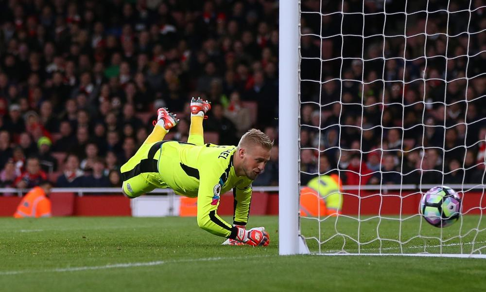 Leicester's Kasper Schmeichel is unable to stop the ball go into the net off his team-mate Robert Huth against Arsenal.