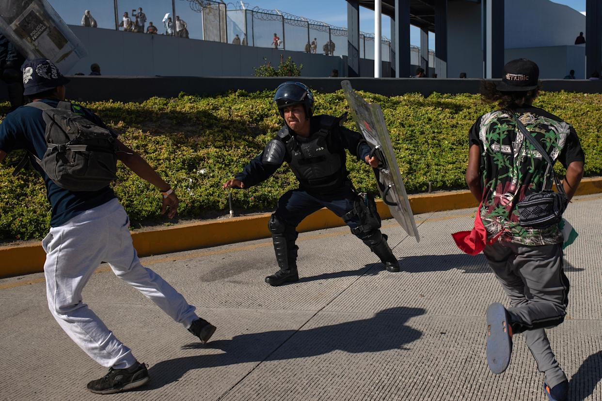 Mexico's Federal Police try to grab migrants, part of a caravan of thousands from Central America, as they attempt to cross the border into the United States from Tijuana, Mexico November 25, 2018. (Photo: Adrees Latif /Reuters)