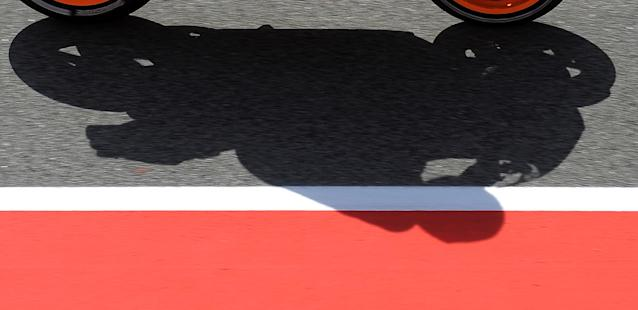 The shadow of Repsol Honda Team's Spanish Dani Pedrosa is pictured at the Catalunya racetrack in Montmelo, near Barcelona, on June 1, 2012, during the MotoGP first training session of the Catalunya Moto GP Grand Prix. AFP PHOTO/LLUIS GENELLUIS GENE/AFP/GettyImages