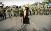 This file photo taken on July 7, 2009 shows Chinese riot police watching a Muslim ethnic Uyghur woman protesting in Urumqi, the capital of China's Xinjiang region