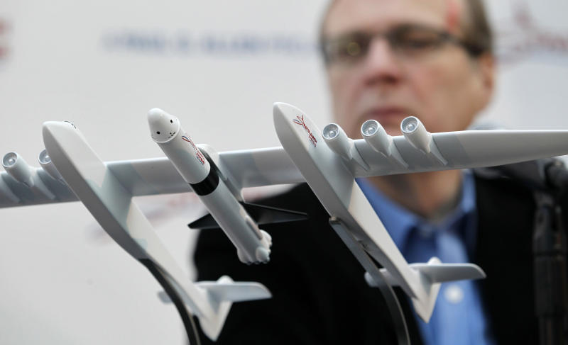 FILE- In this Dec. 13, 2011, file photo Microsoft co-founder Paul Allen looks across at a model of a giant airplane and spaceship he plans on building, during a news conference about the plane in Seattle. Prior to his death on Monday, Oct. 15, 2018, Allen invested large sums in technology ventures, research projects and philanthropies, some of them eclectic and highly speculative. Outside of bland assurances from his investment company, no one seems quite sure what happens now. (AP Photo/Elaine Thompson, File)