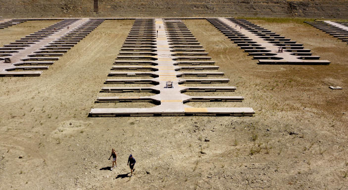 People walk near boat docks as they sit on dry land at the Browns Ravine Cove area of drought-stricken Folsom Lake, currently at 37% of its normal capacity, in Folsom, Calif., Saturday, May 22, 2021. California Gov. Gavin Newsom declared a drought emergency for most of the state. (AP Photo/Josh Edelson)