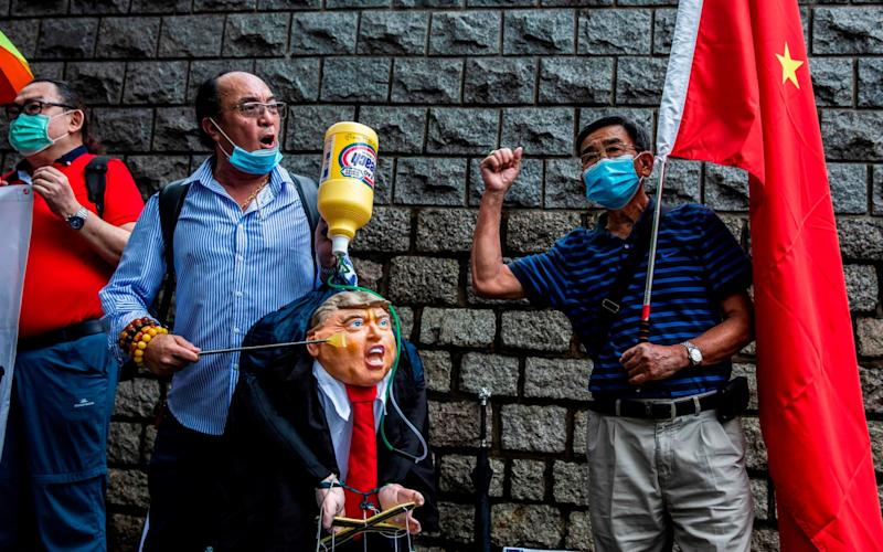 A pro-China activist holds an effigy of US President Donald Trump during a protest outside the US consulate in Hong Kong - ISAAC LAWRENCE/AFP
