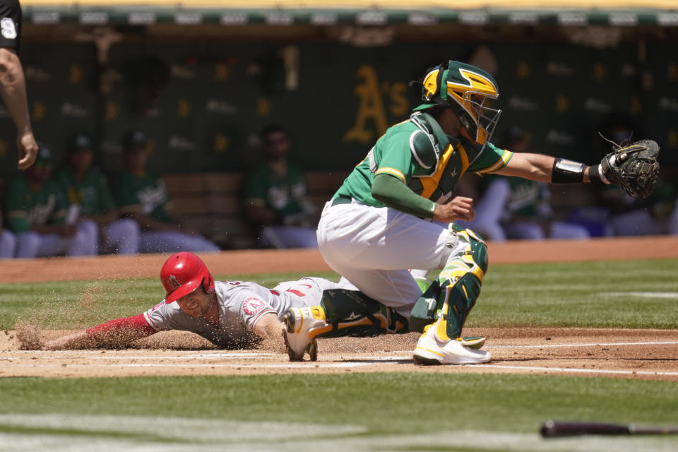Los Angeles Angels' Max Stassi scores at home plate as Oakland Athletics catcher Aramis Garcia waits for the throw in the first inning of a baseball game Wednesday, June 16, 2021, in Oakland, Calif. Stassi scored after the Angels' Taylor Ward singled to left field. (AP Photo/Eric Risberg)