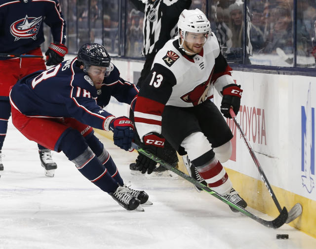 Arizona Coyotes' Vinnie Hinostroza, right, carries the puck across the blue line as Columbus Blue Jackets' Pierre-Luc Dubois defends during the first period of an NHL hockey game Tuesday, Dec. 3, 2019, in Columbus, Ohio. (AP Photo/Jay LaPrete)