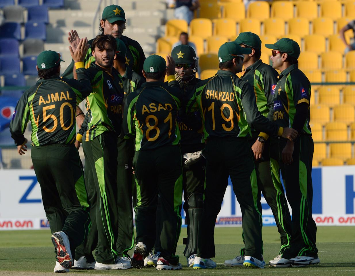Pakistan's wicket keeper Shahid Afridi (2nd L) celebrates with team-mates after taking a wicket of South African batsman Quinton de Kock (unseen) during the third day-night international in Sheikh Zayed Cricket Stadium in Abu Dhabi on Novemver 6, 2013. South African captain AB de Villiers won the toss and decided to bat in the first. The five-match series is tied at 1-1. AFP PHOTO/ Asif HASSAN        (Photo credit should read ASIF HASSAN/AFP/Getty Images)